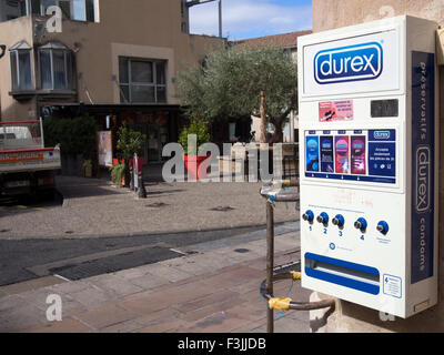 A Durex condom (preventatifs) machine on the outside of a pharmacy in Millau, France. - Stock Image