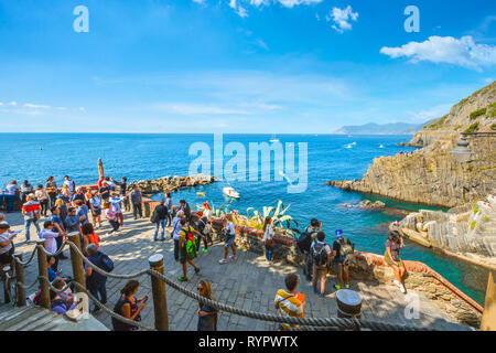 Tourists gather at the lookout point at the Cinque Terre village of Riomaggiore, Italy, with the Ligurian sea, harbor and boats behind them - Stock Image