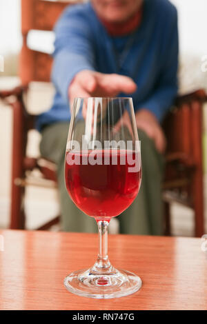 A senior woman sitting down reaching to pick up a glass of red wine on a table in front. UK - Stock Image