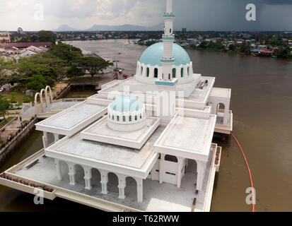 Aerial view (drone) of the Floating Mosque on the Sarawak River in Kuching, with traditional blue dome, spire and also water barrage. - Stock Image