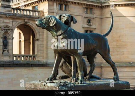 Statue(s) of hunting dogs sculpted in 1880 by Auguste Cain (1821-1894) at the entrance to the Château de Chantilly, Oise, France - Stock Image