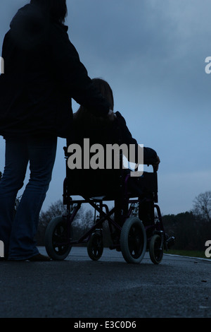 Woman pushing a young girl sitting in a wheelchair. - Stock Image