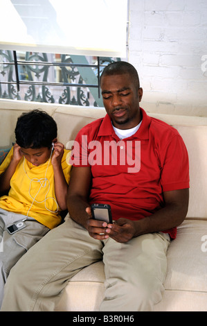 African American father and son engaged with their gadgets - Stock Image