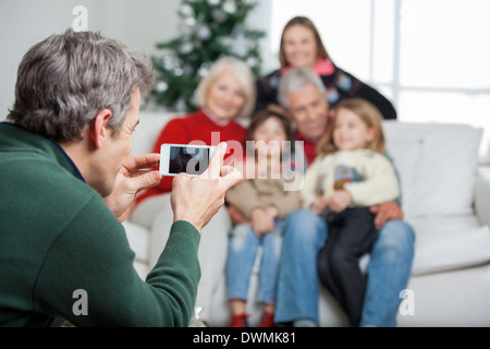 Father Photographing Family Through Smartphone - Stock Image