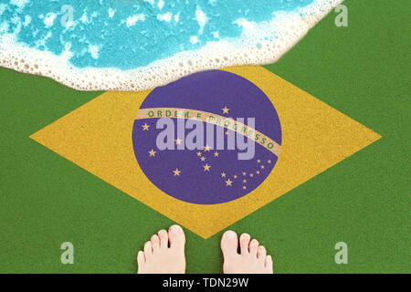 Feet on on sandy beach with flag Brazil. View from top on surf. - Stock Image