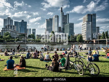 People relaxing at riverside Main, Skyline, banking district, Comerzbank, Frankfurt am Main, Hessen, Germany - Stock Image