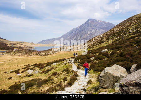 People walking on the path around Llyn Idwal lake in in Cwm Idwal valley in Snowdonia National Park. Ogwen, Conwy, Wales, UK, Britain - Stock Image