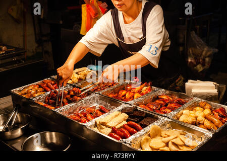 JIUFEN, TAIWAN - NOVEMBER 6: A woman sells traditional Chinese snacks at the street market of Jiufen on November 6, 2018 in Jiufen, Taiawan. - Stock Image