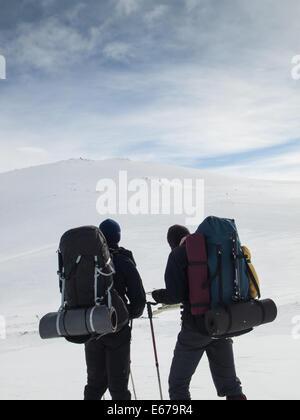 two men with heavy backpacks reading map in winter mountain landscape. Huldraheimen, Gausdal Westfjel, Norway - Stock Image