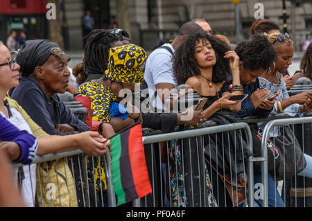 London, UK. 18th August 2018. A person at the front of the audience holds a Pan-African flag at the annual National Memorial event in Trafalgar Square to remember and honour the victims of the African Holocaust/Transatlantic Slave Trade and promote International Slavery Remembrance Day, 23rd August. The event called for Africans to celebrate their identity and to remember their ancestors, and began with libations remembering many black heroes. ers ta Credit: Peter Marshall/Alamy Live News - Stock Image