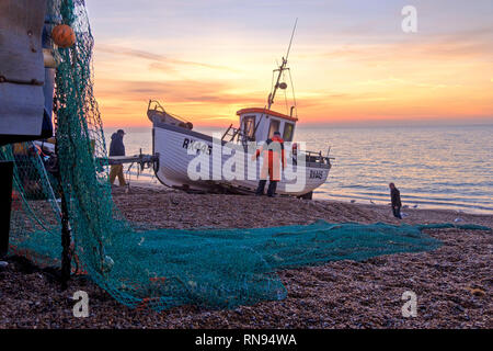 Hastings, East Sussex, UK. Hastings fishing boat being launched at sunrise. Hastings has the largest beach-launched fishing fleet in Europe - Stock Image