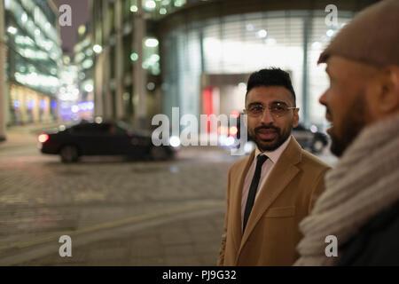 Businessmen talking on city street at night - Stock Image