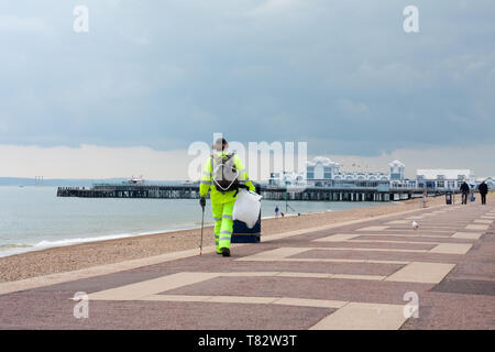 A cleaner keeps the area free of litter at Clarence esplanade, Southsea, Hampshire - Stock Image