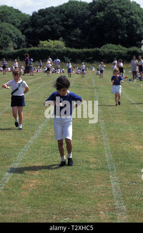 primary school girl in egg and spoon race during sports day - Stock Image