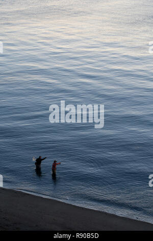 A view from above of a guide and a fly fisherman at the water's edge fishing for salmon and sea run coastal cutthroat trout at a beach on the north we - Stock Image