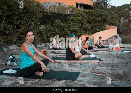 Yoga retreat, group of people sitting and meditating on mats, Puerto Vallarta - Mismaloya, Mexico - Stock Image