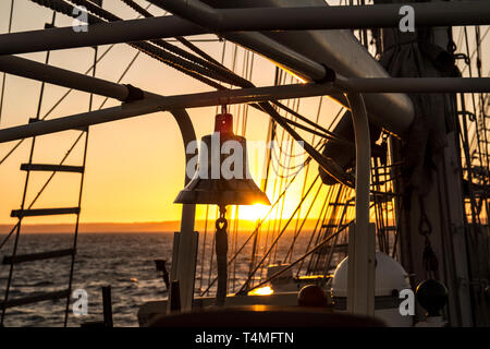 The ships bell at sunset on the Lord nelson barque 3 tall ship - Stock Image