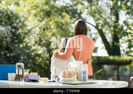 Affectionate mother and daughter on sunny morning patio - Stock Image