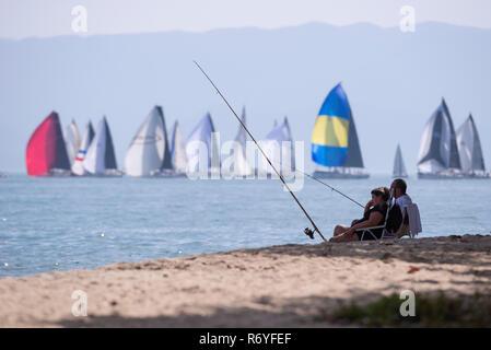 Fishermen enjoying the beach at Ilhabela as sail boats pass by, SE Brazil - Stock Image