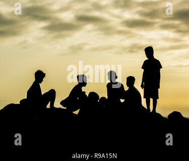 Sillhouete boys at the top of the mountain - Stock Image