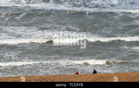 Brighton, UK. 8th June 2019.  Fishermen on Brighton beach today as Storm Miguel passes through Britain bringing wet and windy conditions . Credit: Simon Dack / Alamy Live News - Stock Image