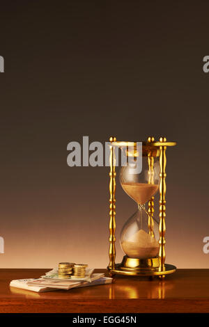 Hour Glass with Money - Stock Image