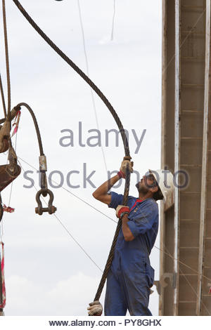 Man wearing hard hat holding cable - Stock Image