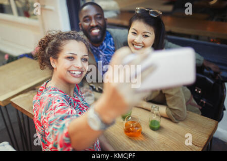 Smiling young friends taking selfie with camera phone at sidewalk cafe - Stock Image