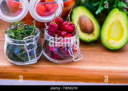 Close up of red hot chilly pepper on wooden table with mangos and other seasonal coloured fresh vegetables  home kitchen food scene - Stock Image