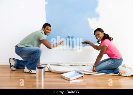 Smiling African American male and female couple painting wall blue - Stock Image