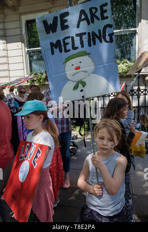 London, UK. 12th May 2019. Children with posters wait for the march by several thousand mothers, children and some fathers behind 11-year-olds and 3 giant push chairs with stilt walkers from Hyde Park Corner to a rally filling Parliament Square, backing Extinction Rebellion's call for the drastic and urgent action needed to avert the worst consequences of climate change, including possible human extinction. Our politicians have declared a climate emergency but now need to take real action rather than continuing business as usual which is destroying life on our planet. Peter Marshall/Alamy Live - Stock Image