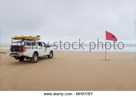Lifeguard Truck Parked Next To Red Danger Flag On Beach In Cornwall - Stock Image