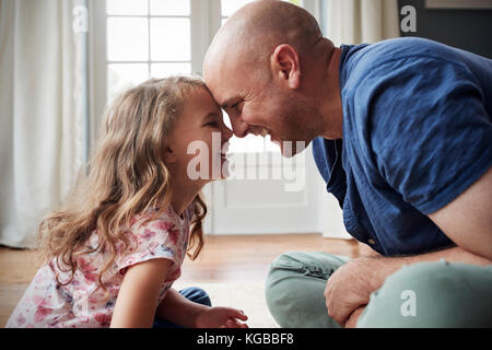Father and daughter sitting on floor at home touching heads - Stock Image