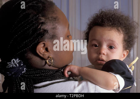 black mother holding her crying toddler - Stock Image