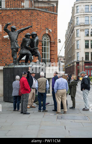 A London tour guide with a group of American tourists at the National Firefighters Memorial statue in Carter Lane Gardens, City of London, England, UK - Stock Image