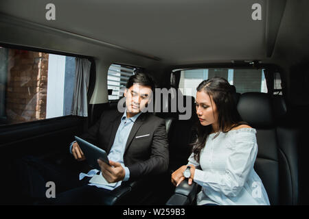 two business people meeting while sitting on passenger seat of car. modern business team on their way for meeting - Stock Image