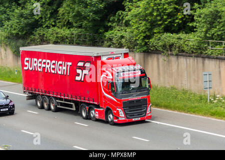 Surefreight branded Volvo FH460 tractor unit with a curtain sided trailer articulated lorry travelling on the M61 motorway near Farnworth. - Stock Image