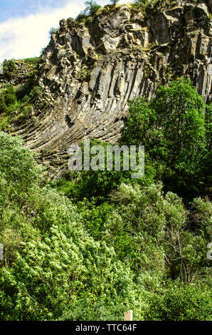 Curved basalt columns on a hill in the Garni gorge among green trees growing along the banks of the Azat river against a blue sky covered with clouds - Stock Image