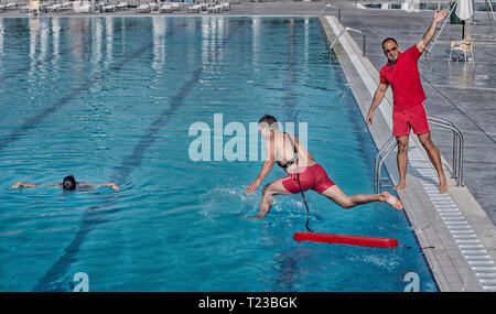 Lifeguard training course - rescuing woman from swimming pool. - Stock Image