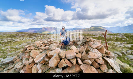 LAKE DISTRICT, CUMBRIA, ENGLAND, UK - SEPTEMBER 02, 2017: A female hiker arrives at the summit shelter of Great - Stock Image