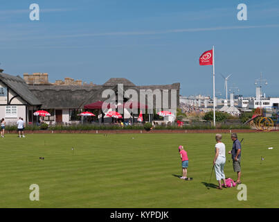 Family enjoying the Putting Green by The Thatch Restaurant on Lowestoft's Seafront, Lowestoft, Suffolk, England, - Stock Image