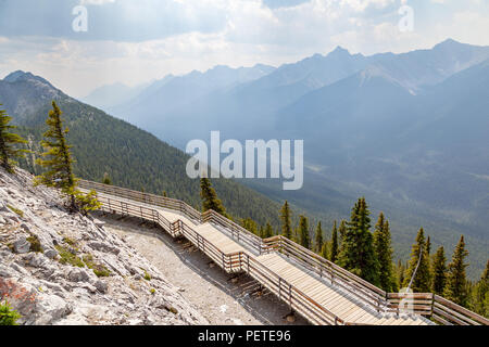 A wooden walkway on top of Sulphur Mountain with panoramic view of the mountain range silhouette in the Canadian Rockies of Banff National Park. - Stock Image