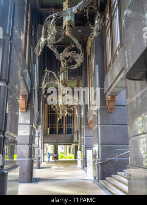 Decorative and ornate metal sculpture and lighting under the granite portico entrance to the plaza in front of the Parkview office tower Singapore. - Stock Image
