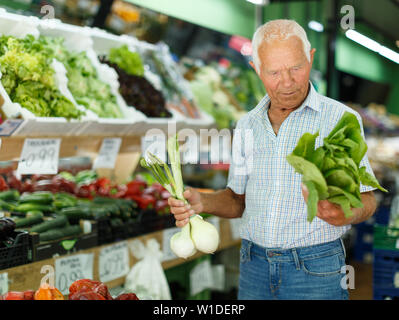 Elderly man looking for fresh organic vegetables in local market - Stock Image