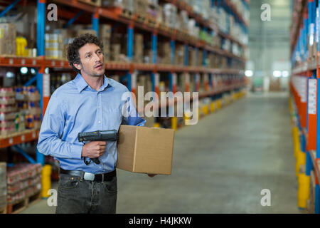 Warehouse worker holding cardboard box and barcode scanner machine - Stock Image