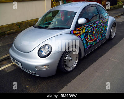 New type Volkswagen Beetle car in silver with artwork painted on the doors - Stock Image