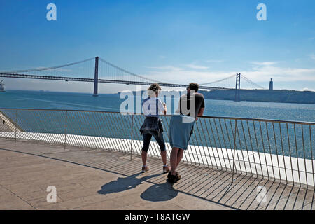 An older couple stop outside MAAT for a view of the 25 April Bridge and the River Tagus Rio Tejo in Belem, Lisbon Portugal Europe EU  KATHY DEWITT - Stock Image