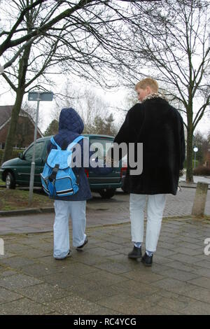 Back view woman picking up a child from school, walking to the car - Stock Image