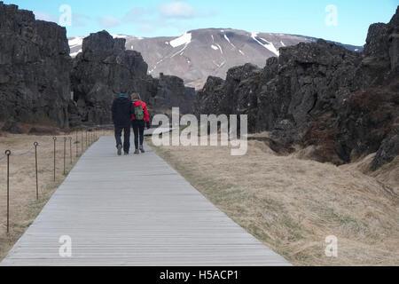 Tourists walking towards high mountain - Stock Image