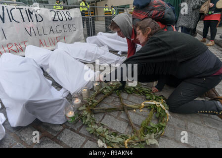 London, UK. 21st December 2018. Climate campaigners from Extinction Rebellion light candles next to the 'bodies' - mannequins wrapped in white cloth to the BBC representing the bodies of a Greek village killed by fire because of global warming. The protest at the BBC called it to stop ignoring the climate emergency & mass extinctions taking place and promoting destructive high-carbon living through programmes such as Top Gear and those on fashion, travel, makeovers etc. It was organised by the Climate Media Coalition (CMC) and its director Donnachadh McCarth . Peter Marshall/Alamy Live News - Stock Image